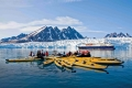 Guests from the Lindblad Expedition ship National Geographic Explorer kayaking near Monaco Glacier on Spitsbergen Island in the Svalbard Archipelago in the summer months. No property or model releases available for this image.